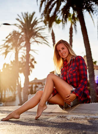 barefoot blonde: Beautiful woman posing at sunset during tropical vacation. Beautiful girl sitting on the curb in shorts and a red shirt. Barefoot blonde girl on the road. Stock Photo