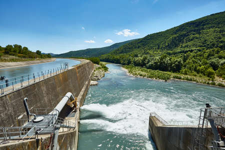 Drain the water from the dam in the mountains.Water rushing through gates at a dam. The dam closeup. Stock Photo