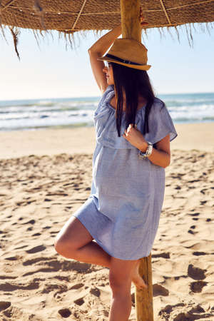 expectant mother: Pregnant young woman on the beach. Beautiful expectant mother in a blue dress and straw hat. She leaned on a sun umbrella. Outdoor shot