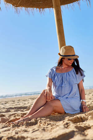 expectant mother: Expectant mother sits on the sand under a sun umbrella. Pregnant young woman on the beach. Outdoor shot