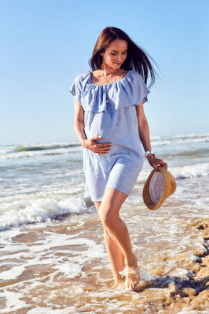expectant: Pregnant woman in blue tunic seashore walk. Expectant mother in a beautiful white dress enjoying a sea holiday. Future motherhood. Stock Photo