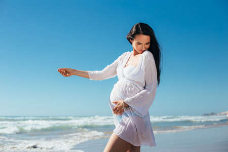 expectant mother: Pregnant having fun on the beach. Expectant mother in white dress on a background of blue sky. Pregnant wearing a tunic seashore walk. Stock Photo