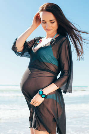expectant mother: Pregnant woman posing on the beach. Expectant mother in a blue dress having fun near the sea. Stock Photo