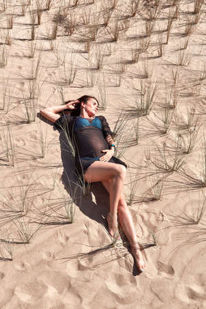 Pregnant lying on the sand and bushes. Pregnant model posing on the sandy background. Beautiful pregnant woman in black dress. Stock Photo