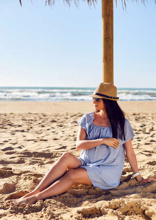 expectant: Expectant mother sits on the sand under a sun umbrella. Pregnant young woman on the beach. Outdoor shot