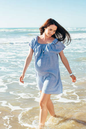 expectant arms: Beautiful pregnant woman walking on blue beach in summer vacation with open arms. Portrait of the young expectant mother. Stock Photo