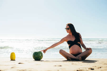 expectant mother: Young happy pregnant woman have fun on the beach. Expectant mother relaxing and enjoying life in nature. Pregnant woman posing near the sea.