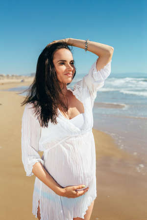 expectant mother: Future young mother in a white dress on the beach. Expectant mother in a beautiful white dress enjoying a sea holiday. Future motherhood.