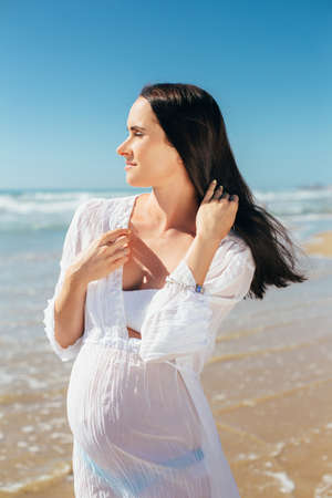 expectant mother: Future motherhood young woman. Expectant mother in a beautiful white dress enjoying a sea holiday. Pregnant wearing a tunic seashore walk Stock Photo