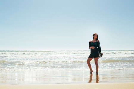 Pregnant woman posing on the beach. Holding belly over sea background. Motherhood. Maternity.