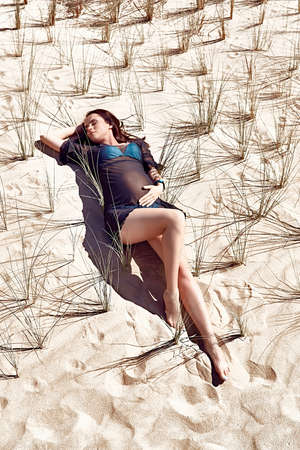 expectant mother: Pregnant model posing on the sandy background. Expectant mother lying on the sand and bushes.