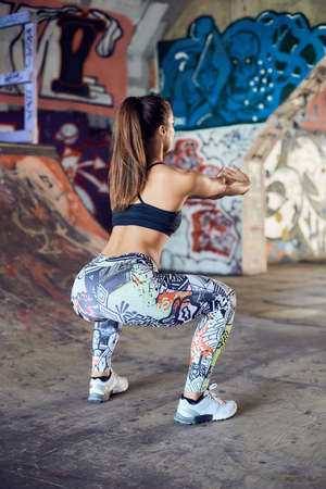 Athletic young woman doing squat exercises for the buttocks. Fitness model working out on the urban city background. Pretty young woman training to stay fit and healthy.