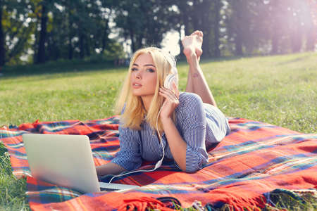 woman resting: Girl lying on the green grass and listening to music. Blonde woman resting on a red blanket with a laptop. Outdoor. Sunny day. Back to school. Stock Photo