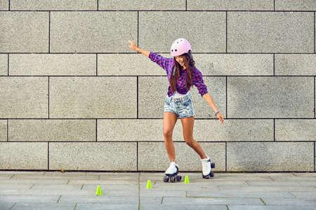 ヘルメットで美しい少女はバランスを持ってローラー スケート乗ってを学習します。都市の灰色の背景上の美しい少女ローラーブレードとスピン ス