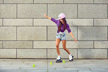 Beautiful girl in a helmet learns to ride on roller skates holding a balance. Beautiful girl rollerblading and spin slalom element on the urban grey background.