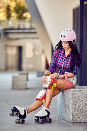 Active lifestyle girl is going to ride on roller skates. Beautiful girl puts protection equipment for rollerblading. Attractive teenager sitting on street a sunny day. Stock Photo