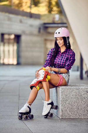 knee pads: Young sporty woman and skating protection equipment. Beautiful girl puts on protective gear for rollerblading. Stylish pink skating helmet, knee pads and quad roller skate. Stock Photo