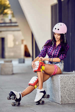 knee pads: Beautiful girl puts on protective gear for rollerblading. Stylish pink skating helmet, knee pads and quad roller skate.