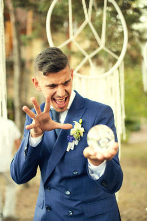honeymooner: Groom holding a crystal ball and casts a spell. Honeymooner have fun at a wedding in the woods in a rustic style. Stock Photo