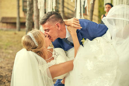 passionate kiss: Passionate kiss of newlyweds at the wedding in the woods in a rustic style.