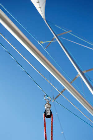 spinnaker: The spinnaker pole is rigged to run from the base of the mast to windward over the side of the boat. For a spinnaker, the line attached to the pole is the guy, or brace, and the corner is the tack Stock Photo