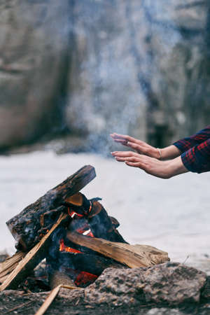 warms: Girl warms hands near a fire in winter. Rocks on background