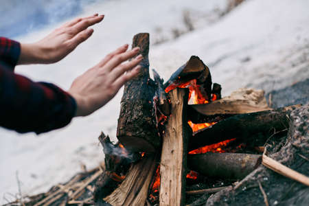 Girl warms hands near a fire in winter. Rocks on background