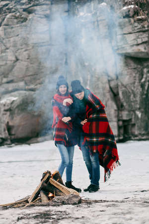 Guy and girl at a picnic. They bask with blanket near the bonefire. hey are happy and are pleased of life Stock Photo