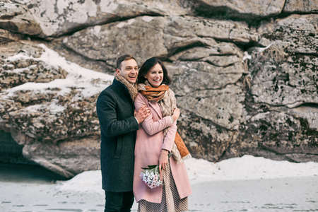 love very: Winter love story. Cute couple in a very beautiful place. They laugh at the frozen lake near high rocks