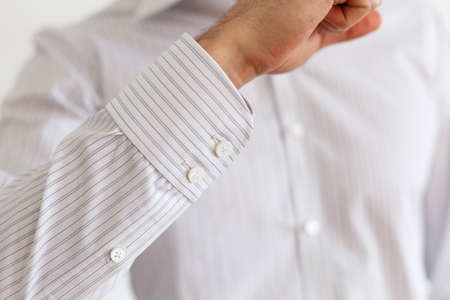 french cuffs: Sleeve of a white shirt. Buttons on Cuffs. close up view