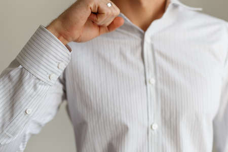 cuff: Sleeve of a white shirt. Buttons on Cuffs. close up view