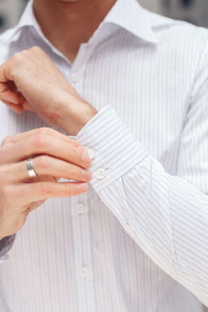french cuffs: Man buttons cuff-link on French cuffs sleeves luxury white shirt. Close up of a businessman showing a shirt cuff. Stock Photo