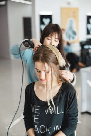 Kyiv, Ukraine - March 3, 2017: The hairdresser does the styling for the girl. Preparation for the wedding in the morning in the salon.