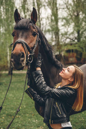 Beautiful girl communicates with the horse in the park. Preparing for the riding