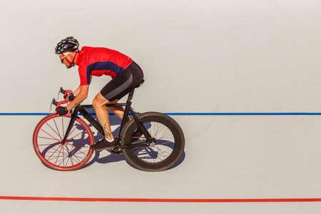 競輪場の屋外の競技の選手。赤い t シャツと黒の自転車プロ選手。