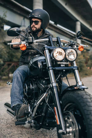 Biker in helmet and leather jacket sitting on a motorcycle. Freedom and travel concept.