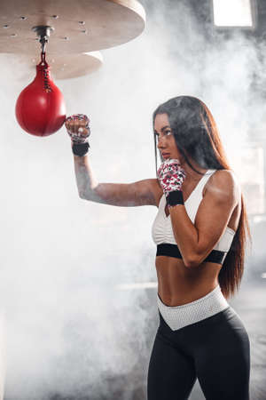 Beautiful woman with the pink boxing wraps in the rays of the sun and smoke. The concept of a healthy lifestyle.