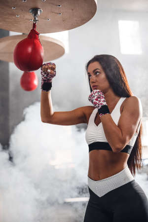 Female boxer in the rays of the sun and smoke background. Attractive girl training with the pink boxing.
