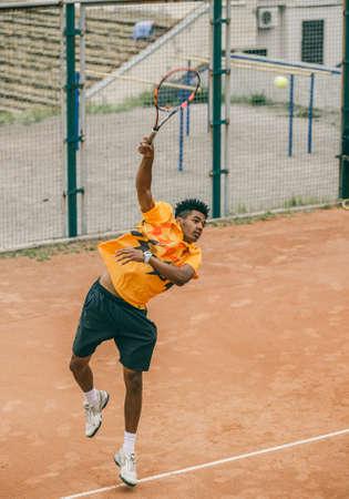 若い男は、テニス ラケットでボールを打ちます。テニス プレーヤーは、テニスコートの決闘を保持します。
