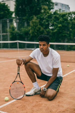 Young man hanging out in the tennis courts sitting on ground. African man resting and chilling on the break time. Stock Photo