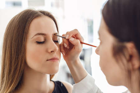 plucking: Beautiful young woman gets eyebrow correction procedure. Young woman tweezing her eyebrows in beauty saloon.