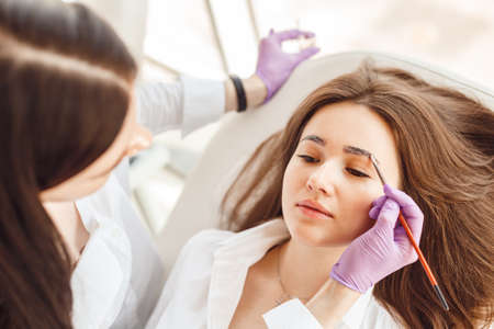 Top view of a woman a client lies on the procedure for eyebrow correction. Young women tweezing her eyebrows in beauty salon. Stock Photo