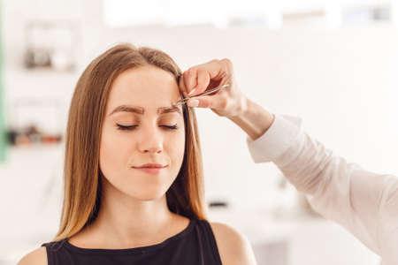 マスターの化粧は訂正し、鉗子のサロンで眉を引き出して形を与えます。顔のプロフェッショナルケア