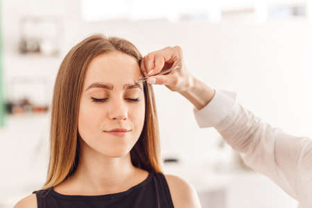 Master makeup corrects, and gives shape to pull out with forceps eyebrows in a beauty salon. Professional care for face