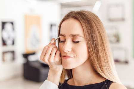 plucking: Young woman tweezing her eyebrows in beauty saloon. Young woman plucking eyebrows with tweezers close up