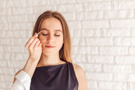plucking: Portrait of a model and the masters hand with tweezers. Young woman tweezing her eyebrows.
