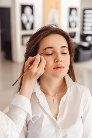 Cropped view of a young woman having brow color added to her eyebrows. Cosmetologist making a service to the young woman in the salon.