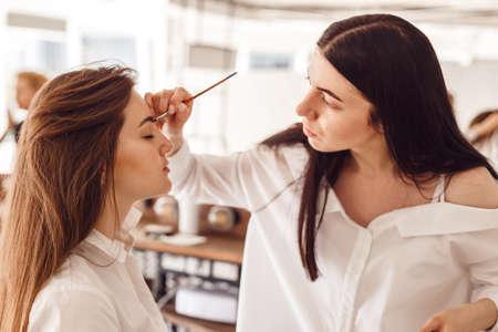Correctie van wenkbrauwpincet, wenkbrauwhenna-schilderij, mooie jonge meisjessalon, perfecte wenkbrauwen. Professionele zorg voor gezicht.