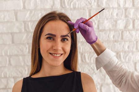 ヘナ色の眉毛と魅力的な若い女性のお客様。顔の専門家の治療です。 写真素材 - 80891794