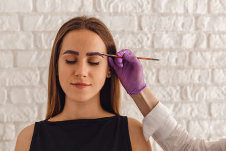 Attractive young woman customer with henna-colored eyebrows. Professional care for face. Stock Photo